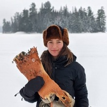Young woman wearing winter hat holds piece of wood in front of snow covered trees