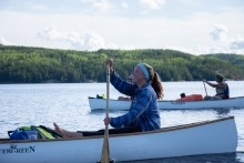 Smiling woman on a canoe