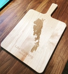 """Wooden charcuterie board with """"Lake Winnipeg, Manitoba"""" as well as an outline of the lake engraved on it"""