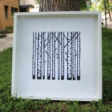A black-and-white linocut print of birch trees