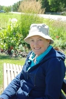 Photo of Nancy Loadman, member of our Science Advisory Council, on a bench in front of flowers.