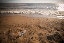 A single-use plastic water bottle in the sand on a Lake Winnipeg beach