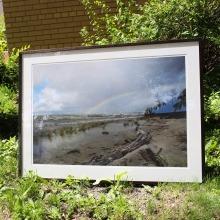 A framed photograph of a rainbow over a Lake Winnipeg beach