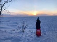 A woman wearing a ribbon dress looks over a frozen Lake Winnipeg at an orange sunset.