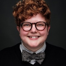 A studio photo of Saz Massey smiling.